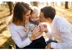 一对年轻夫妇带着一个小男孩走在树林里_3280601