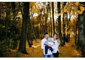 一对年轻夫妇带着一个小男孩走在树林里_3280603