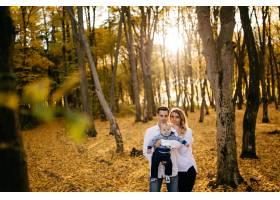 一对年轻夫妇带着一个小男孩走在树林里_3280604