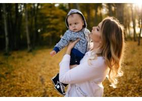 一对年轻夫妇带着一个小男孩走在树林里_3280607
