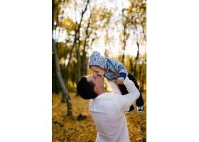 一对年轻夫妇带着一个小男孩走在树林里_3280610