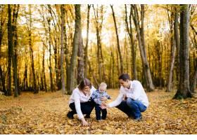 一对年轻夫妇带着一个小男孩走在树林里_3280611