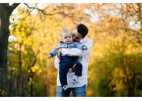 一对年轻夫妇带着一个小男孩走在树林里_3280613