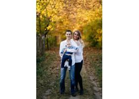 一对年轻夫妇带着一个小男孩走在树林里_3280614