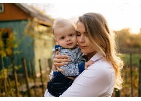 一对年轻夫妇带着一个小男孩走在树林里_3280615
