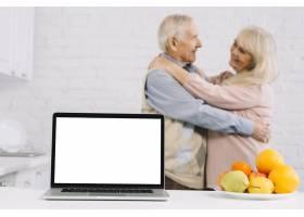 厨房里的高年级夫妇在笔记本电脑后面跳舞_3553483