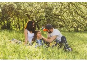 父母带着女儿坐在绿草地上_2572818