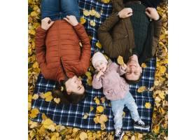 父母带着女儿躺在公园的秋叶上_2816501