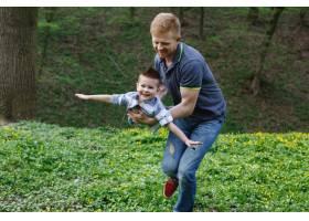 爸爸像一架在绿色公园里玩耍的飞机一样旋转_2438060