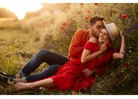 男人抱着他的女人温柔地和她坐在绿色的草坪_2914009