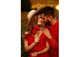 男人抱着娇嫩的美女和她一起站在绿色的田_2914017