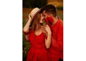 男人抱着娇嫩的美女和她一起站在绿色的田_2914018