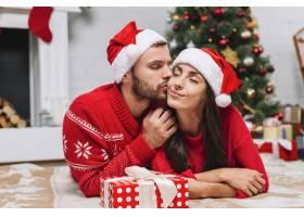 男子在圣诞树附近亲吻女子_3180798