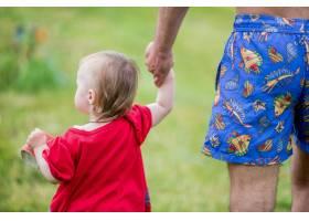 穿着红色连衣裙的小女孩牵着父亲的手走过田_2631520