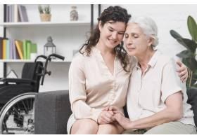 年幼的女儿坐在沙发上拥抱她的母亲_2698321