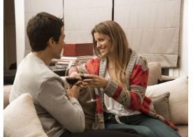 年轻夫妇坐在沙发上享受饮料_3165857
