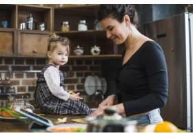 年轻女子在女儿身边做饭_2329627
