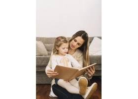 年轻女子在沙发旁给女儿读书_2925010