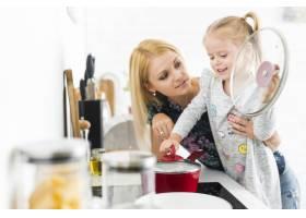 年轻女子带着女儿在厨房里_2689838