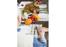 年迈的夫妇坐在节日的餐桌前_3170890