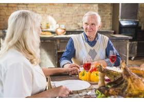 年迈的夫妇端着食物坐在餐桌旁_3180689