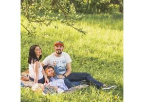 幸福的夫妇带着他们的女儿在花园里玩耍_2572754