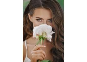 可爱的年轻女子在她面前捧着白花_2612732