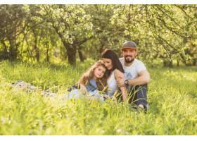 在夏天愉快的家庭坐在绿色的草地上_2572792