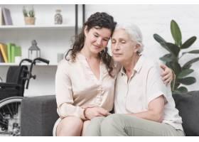 坐在家里沙发上拥抱年长母亲的母亲_2698304