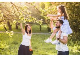 坐在父亲肩上的女孩和母亲一起摘树叶_2586669