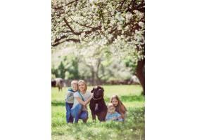 坐在草地上的母亲孩子和狗_2916335