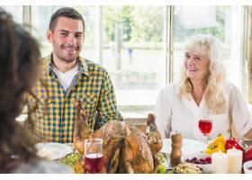 坐在餐桌旁的男士和面带微笑的老年女士_3170900