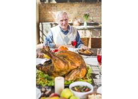 坐在餐桌旁端着食物的老人_3170931