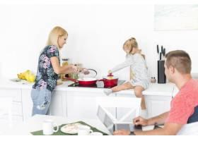 一个男人看着她的妻子和女儿在厨房工作_2689785