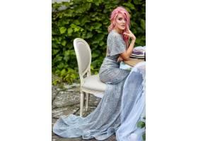 一位优雅的粉色头发的女人穿着银色连衣裙坐_1621127