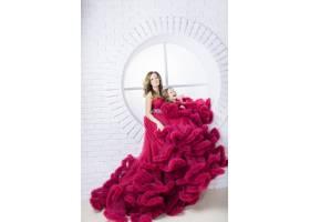 一位穿着粉色连衣裙的妇女和她的小女儿坐在_2612728