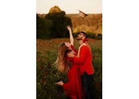 一名女子抛起她的干草帽与她的男子站在一_2914021