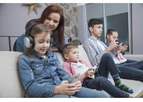 一名妇女看着孩子们玩电子游戏_2041357