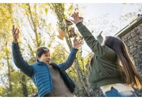 一名男子和他的女儿在公园里玩干燥的秋叶_2579771
