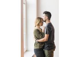 一名男子在家中拥抱她的女朋友在她的额头_2718734