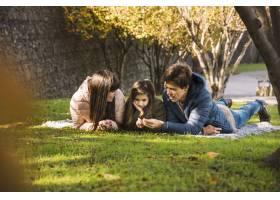 一家人在公园里看着干燥的秋叶_2579791