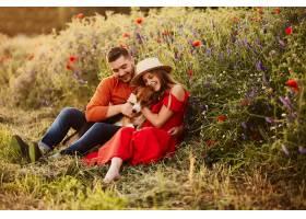 一男一女和一只有趣的小猎犬坐在绿色的田野_2914007