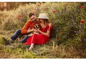 一男一女和一只有趣的小猎犬坐在绿色的田野_2914008