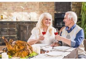 上了年纪的男人和女人拿着眼镜在烤鸡附近_3187250