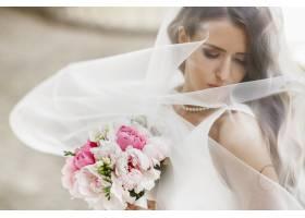 令人惊叹的新娘在外面的面纱下摆姿势的照片_2612744