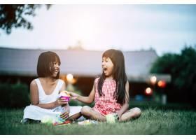 两个小女孩在自家花园里玩玩具_2525647