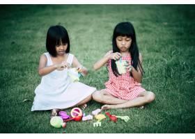 两个小女孩在自家花园里玩玩具_2525648