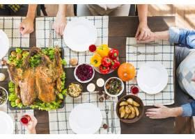 人们坐在餐桌旁端着不同的食物_3170913