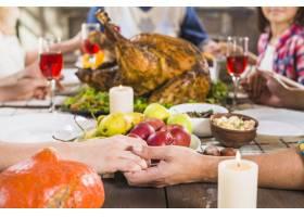 人类在餐桌上牵着手拿着食物_3180717