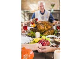 人类在餐桌上牵着手拿着食物接近年长的_3180720